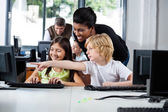 Teacher Assisting Boy Pointing On Computer In Lab — Stock Photo