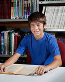 Teenage Male Student Sitting At Table In Library — Stock Photo