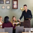 Young Waiter Giving Menu To Female Customers — Stock Photo