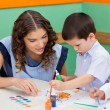 Boy Painting While Teacher Assisting Him — Stock Photo