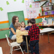 Stock Photo: Teacher Playing With Children In Kindergarten