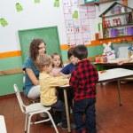 Teacher Playing With Children In Kindergarten — Stock Photo #27799145