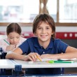 Happy Little Boy Sitting At Desk — Stock Photo