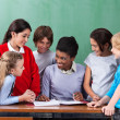 Stock Photo: Happy Teacher Teaching Schoolchildren At Desk In Classroom