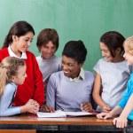 Happy Teacher Teaching Schoolchildren At Desk In Classroom — Stock Photo