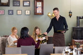 Young Waiter Giving Menu To Female Customers — Stockfoto
