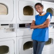 Female Helper Leaning On Dryers In Laundry — Stock Photo