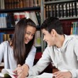 Girl Holding Boy'S Hand While Sitting In Library — Foto de Stock