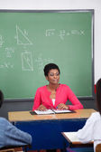 Teacher Sitting At Desk With Students In Foreground — Stock Photo