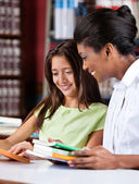 Librarian And Schoolgirl Looking Together At Book — Stock Photo