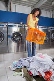 Woman Holding Empty Basket With Clothes On Floor — Stock Photo