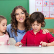 Stock Photo: Teacher With Children Using Digital Tablet At Desk