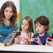 Teacher Teaching Students To Play Xylophone In Class — Stock Photo #27939879
