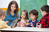Teacher Teaching Students To Play Xylophone In Class — Stock Photo