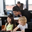 Stock Photo: Teacher Assisting Schoolchildren In Using Desktop Pc