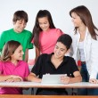 Teenage Boys And Girls Using Digital Tablet At Desk — Stock Photo #27941369