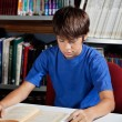 Teenage Schoolboy Reading Book In Library — Stock Photo #27947119