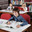Boy Sitting At Table With Books With Classmates In Background — Stock Photo