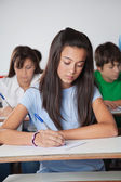 Female Student Writing Paper At Desk In Classroom — Stock Photo