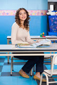 Teacher With Popup Book Sitting At Desk In Preschool — Stok fotoğraf