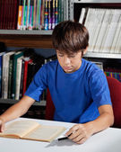 Teenage Schoolboy Reading Book In Library — Stock Photo
