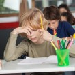 Bored Schoolboy Sitting At Desk In Classroom — Stock Photo