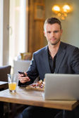 Businessman With Mobilephone And Laptop Having Food — Stock Photo