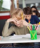 Entediado estudante sentado à mesa na sala de aula — Fotografia Stock
