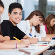 Teenage Boy Sitting With Friends Writing At Desk — Stock Photo