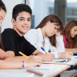 Teenage Boy Sitting With Friends Writing At Desk — Stockfoto