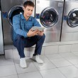 Man Using Digital Tablet While Sitting Against Washing Machines — Stock Photo