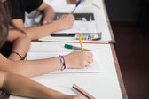 Midsection Of Schoolchildren Writing At Desk — Foto Stock