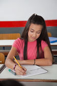 High School Student Writing In Book At Desk — Stock Photo