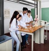 Nauczyciela z uczniami za pomocą cyfrowego tabletu w pracowni — Zdjęcie stockowe