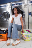Cheerful Woman Sitting In Laundry — Stock Photo