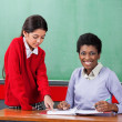 Portrait Of Teacher With Girl Pointing On Binder At Desk — Stock Photo #28310105
