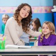 Teacher With Arm Around Little Girl In Classroom — Stock Photo #28330655