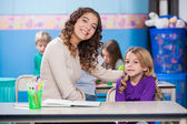 Teacher With Arm Around Little Girl In Classroom — Stock Photo