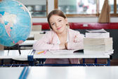 Cute Schoolgirl Sitting With Globe And Stacked Books — Stock fotografie