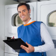 Male Helper Writing On Clipboard In Laundry — Stock Photo