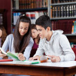 Stock Photo: Teenage Classmates Reading Book In Library