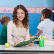 Teacher Writing In Book With Children In Background — Stock Photo