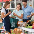 Saleswoman Showing Vegetable Packet To Couple — Stock Photo