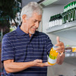 Senior Male Customer Buying Juice Bottle — Stock Photo
