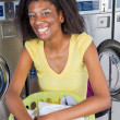 Woman With Basket Of Clothes In Laundromat — Stock Photo