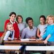 Happy Teacher And Schoolchildren Together At Desk In Classroom — Stock Photo