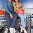 Happy Young Couple Sitting On Washing Machines — Stock Photo