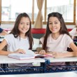 Portrait Of Happy Schoolgirls Sitting With Book At Desk — Foto de Stock