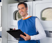 Auxiliar masculino escrevendo na área de transferência na lavanderia — Fotografia Stock