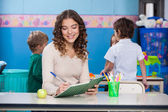 Leraar in boek met kinderen op achtergrond schrijven — Stockfoto